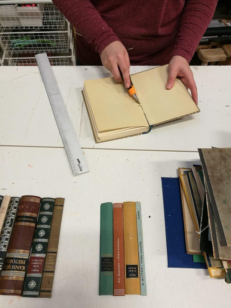 Kuvassa Ekotuunarin asiakas leikkaa vanhaa kirjaa.