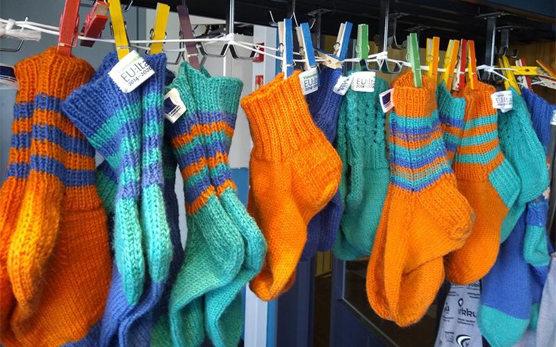 Värikkäitä sukkia ripustettuna naulakkoon.