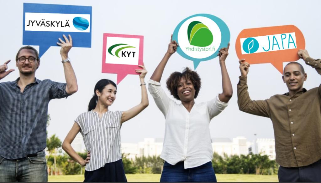 Neljä ihmistä seisoo vierekkäin iloisina ja pitää käsissään kylttejä, joissa KYTin, JAPAn, Jyväskylän ja Yhdistystorin logot